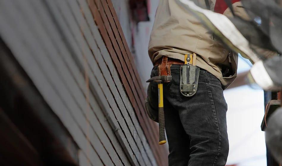 Håndværker med hammer og andet udstyr ved bukserne