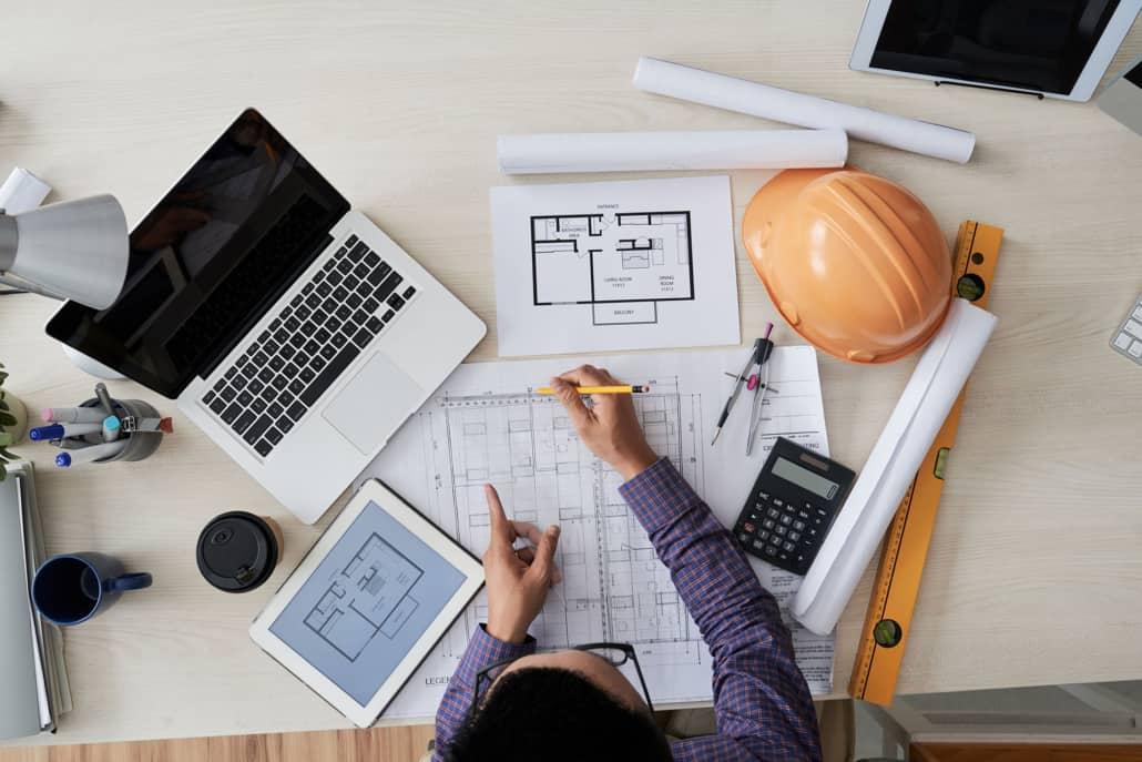 planlægning af byggeprojekt med byggetegninger og computer