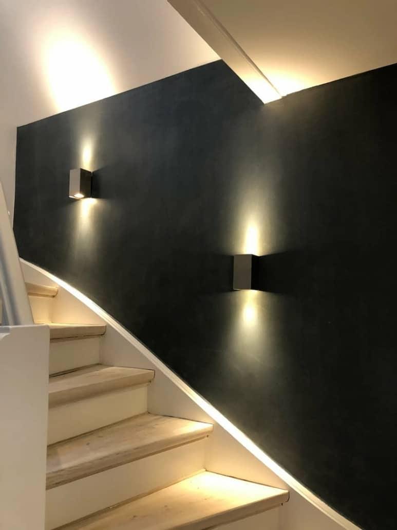 trappeopgang med sorte vægge og væglamper