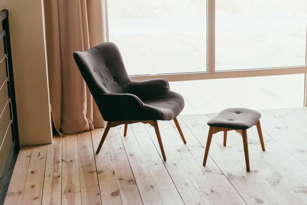 Trægulv under skandinavisk stol nær vindue