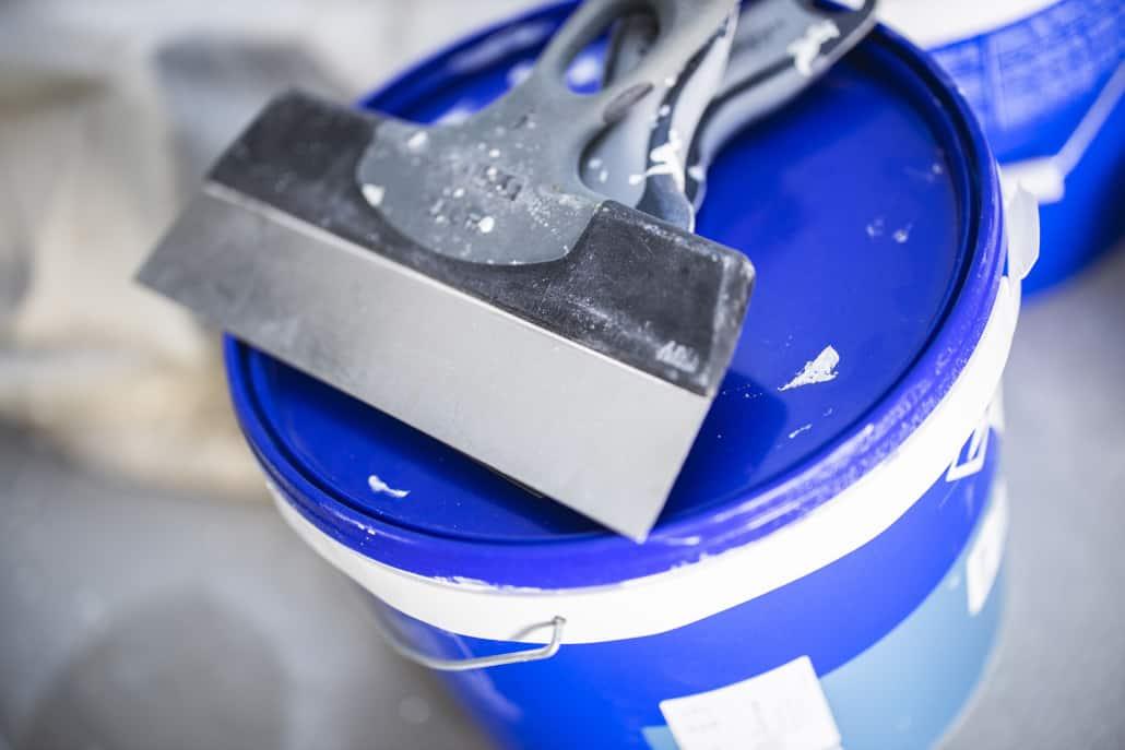Spartel på blå malerspand