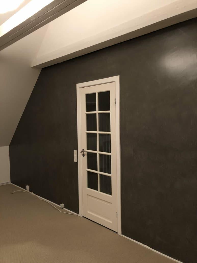 Nymalet sort væg med hvid glasdør