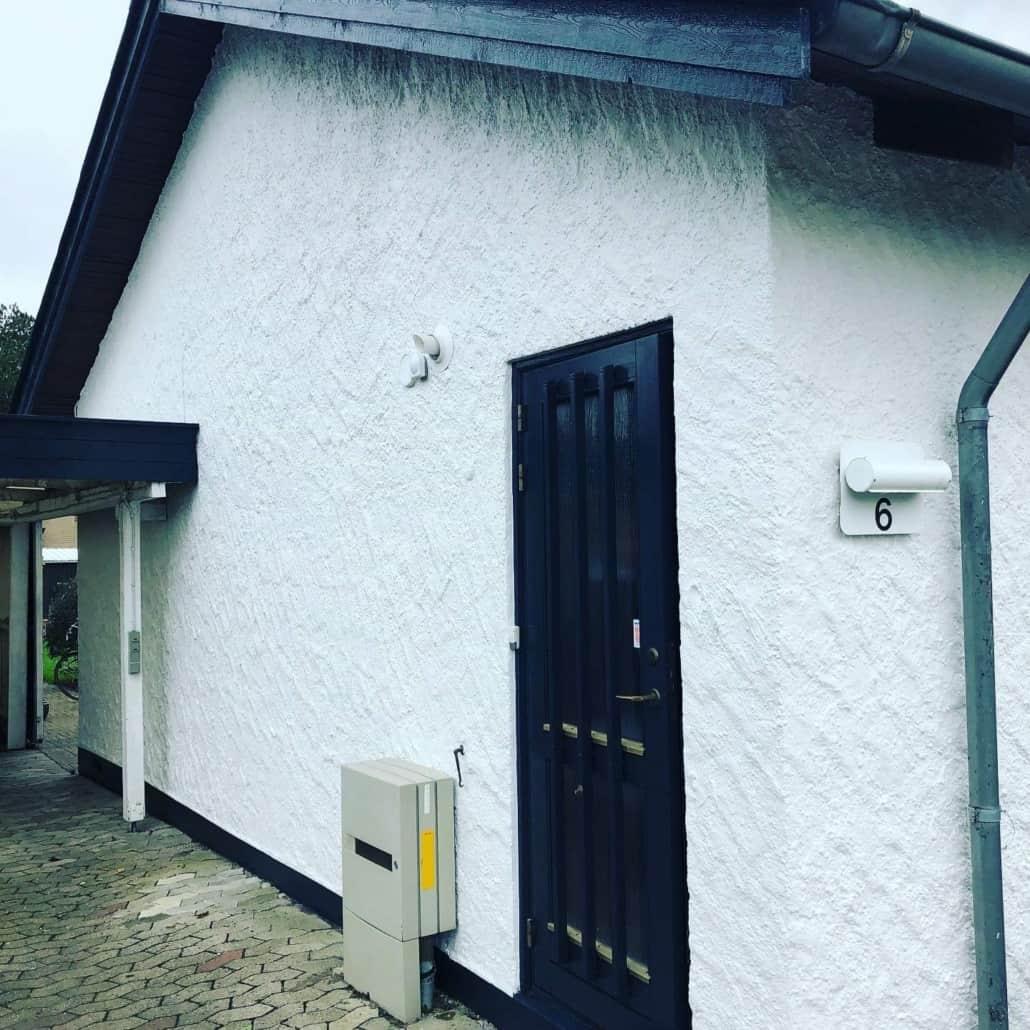 Hus med hvide vægge og sort tag